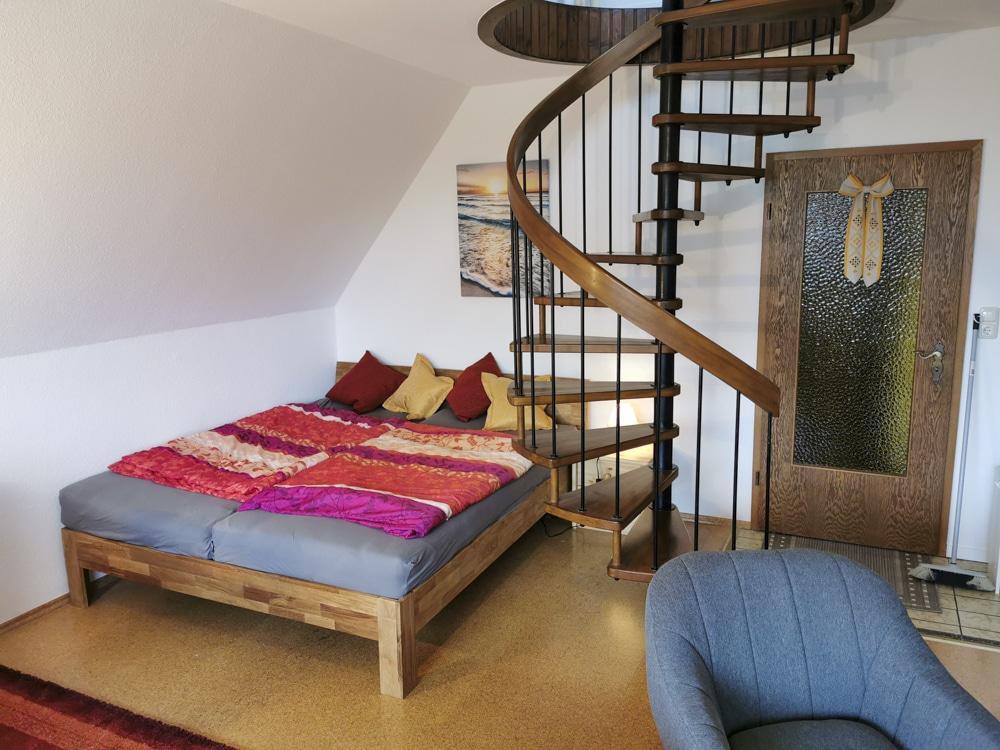 FeWo_Deichblick-21-Stinteck-Haus-Deichlaeufer_Wohnbereich-Bett-Wendeltreppe